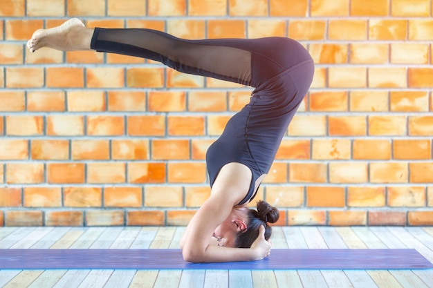 Asian trainee strong woman practicing difficult yoga rajakapotasana king pigeon pose Premium Photo