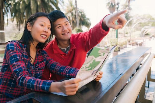 Азиатские пары путешественника держа карту и ища направления. Бесплатные Фотографии
