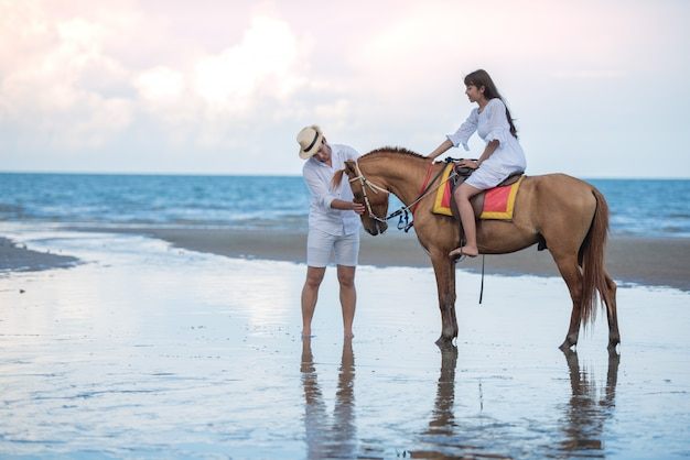 Asian traveling woman riding a horse and take care with his boy friend at sea beach. Premium Photo