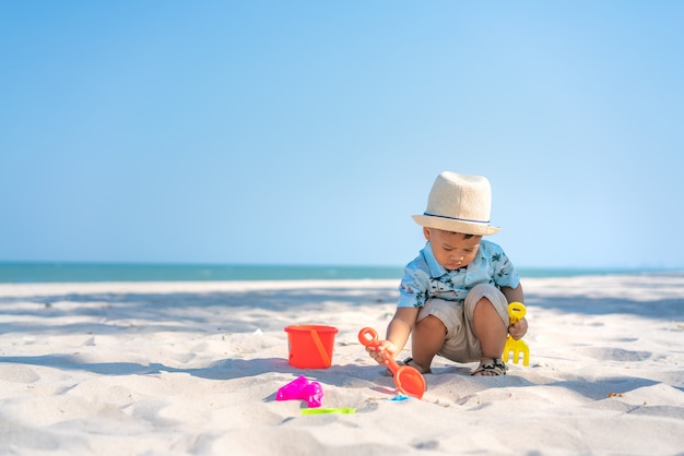 Asian two year old toddler boy playing with beach toys on beach. Premium Photo