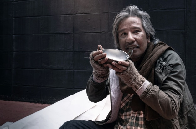 Asian vagrant feel happy with the donated milk, homeless and hungry vagrant holding a cup of milk Premium Photo