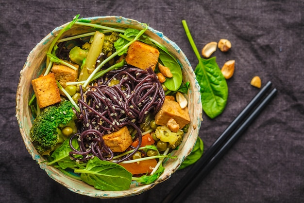 Asian vegan stir fry with tofu, rice noodles and vegetables, dark background. Premium Photo