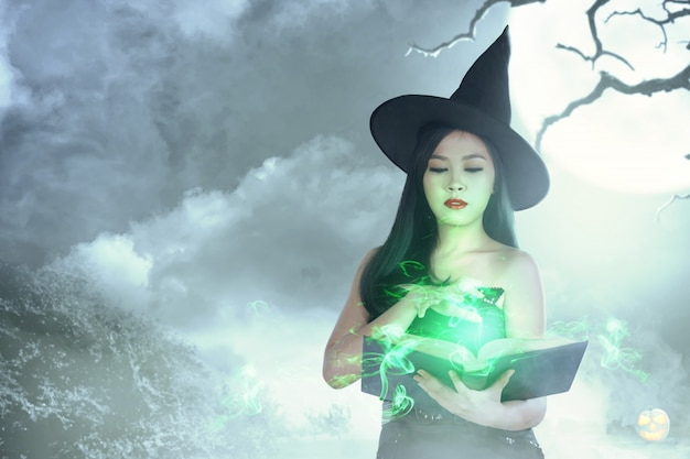 Asian witch woman in hat learns the spell from the magic book Premium Photo
