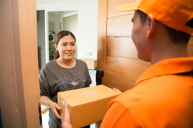 Asian woman accepting a delivery of boxes from deliveryman Premium Photo