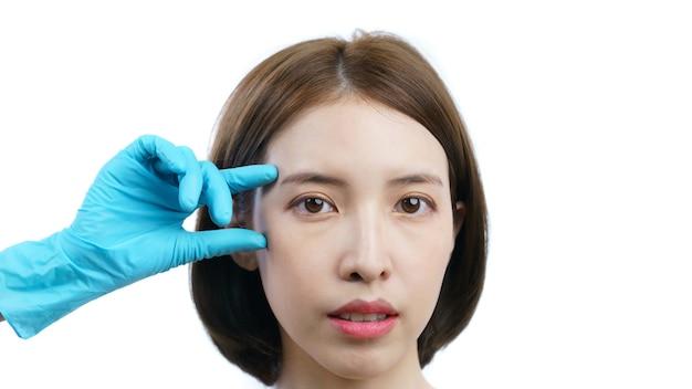健康な肌と白で隔離整形手術の前にチェックアイに触れるアジアの女性と医師 Premium写真