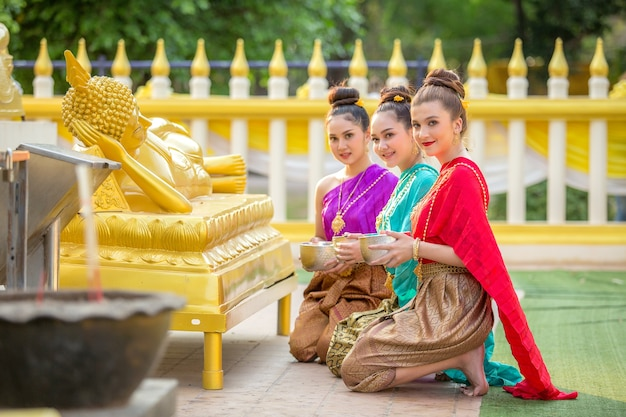 Asian woman are bathing buddha statue happily in thailand. Premium Photo
