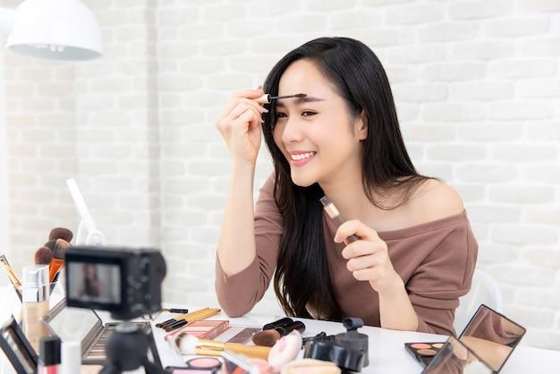 Asian woman beauty vlogger doing cosmetic makeup tutorial video Premium Photo