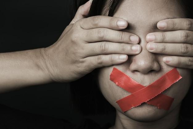 Азиатская женщина с завязанными глазами заворачивает рот красной липкой лентой Premium Фотографии