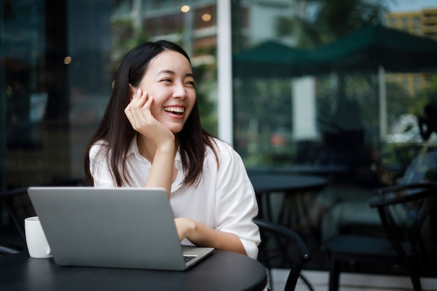 Asian woman at a cafe working on a laptop Premium Photo