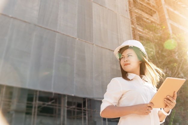 Asian woman civil engineer with white safety helmet visit construction site. Premium Photo