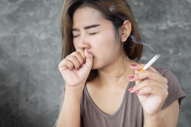 Asian woman coughing from smoking cigarette Premium Photo