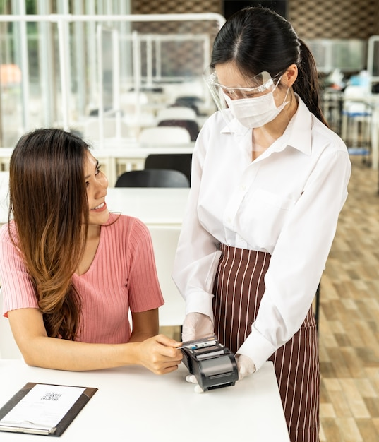 Asian woman customer make contactless credit card payment after eating out in new normal social distance restaurant to reduce touching. online contactless and technology concept. Premium Photo