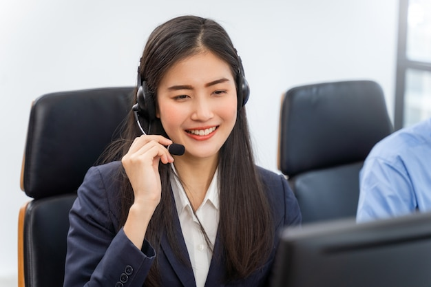 Asian woman customer service agent with headsets working on computer Premium Photo