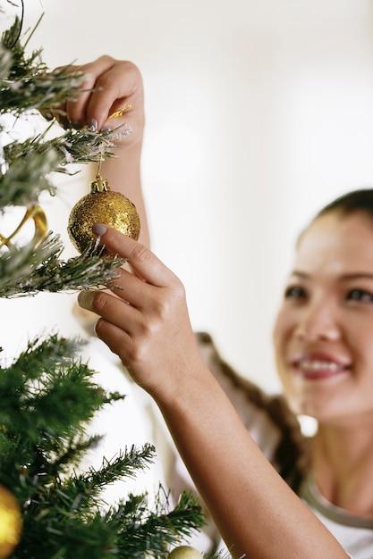 크리스마스 트리를 장식하는 아시아 여자. 무료 사진