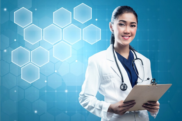 Asian woman doctor in white lab coat and stethoscope holding clipboard Premium Photo