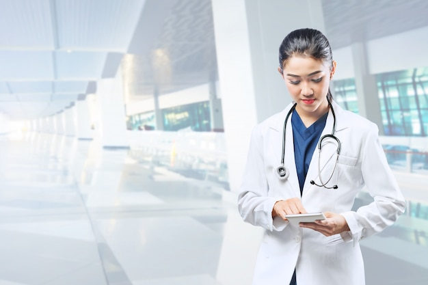 Asian woman doctor in white lab coat and stethoscope using tablet Premium Photo