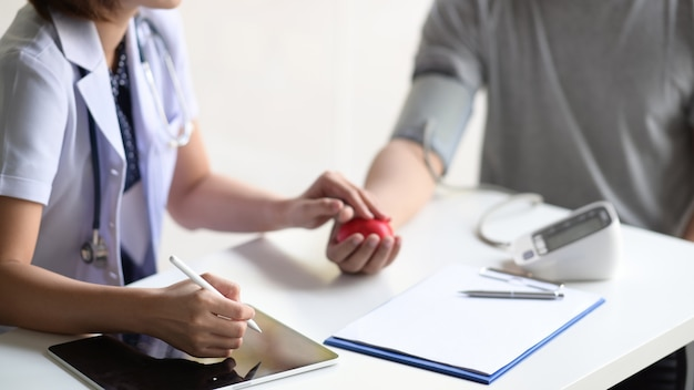 Asian woman doctor with tablet talking to male asian patient in office Premium Photo