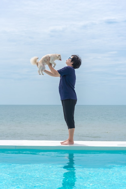 Asian woman and dog hugging on white beach bed at swimming pool Premium Photo