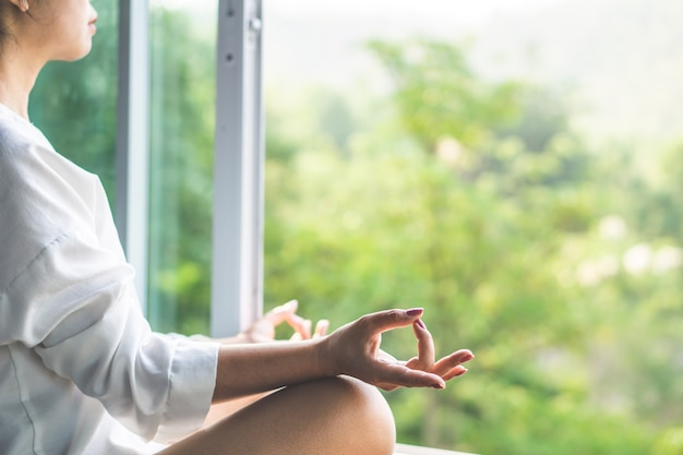 Asian woman doing yoga and meditating with nature Premium Photo