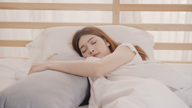 Asian woman dreaming while sleeping on bed in bedroom Free Photo