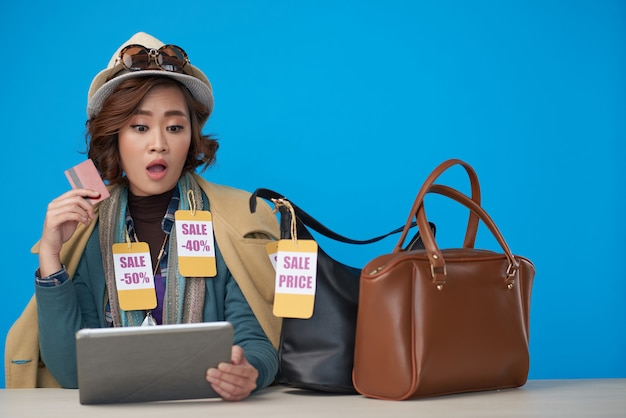 Asian woman, dressed in new clothes with discount labels, sitting with tablet and credit card Free Photo
