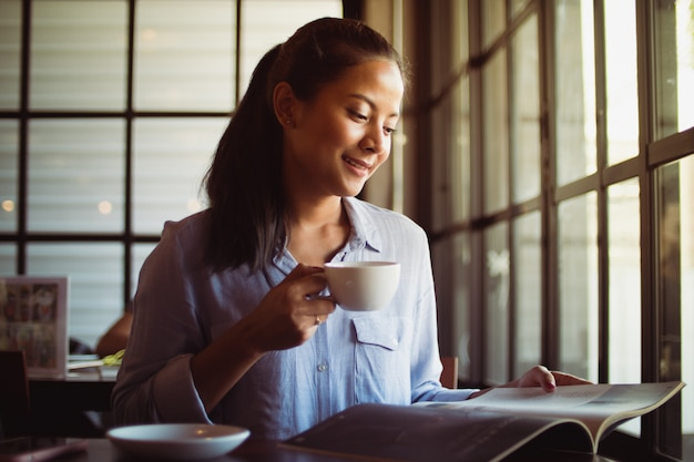 Asian woman drinking coffee in cafe Premium Photo