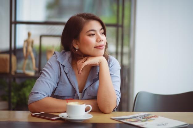 Азиатская женщина, пить кофе в кафе кафе и с помощью мобильного телефона Premium Фотографии