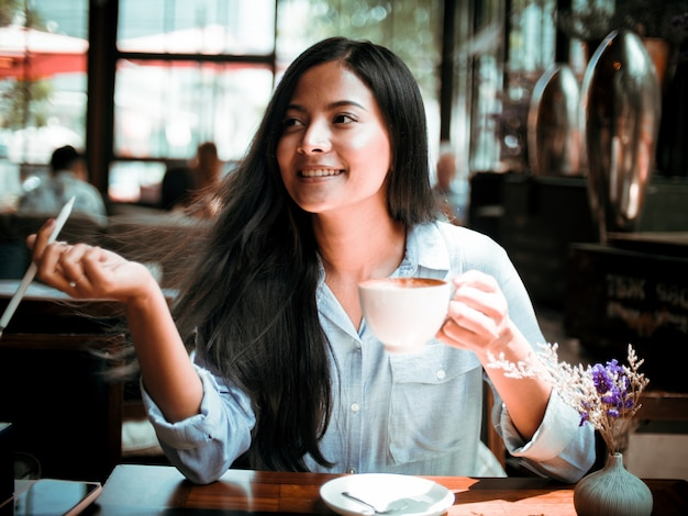 Asian woman drinking coffee and working with laptop computer in cafe Premium Photo