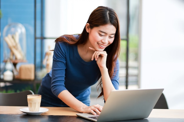 Asian woman drinking coffee and working with laptop computer Premium Photo