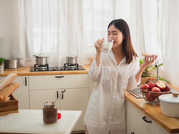 Asian woman eating bread and drink milk  in the kitchen Premium Photo