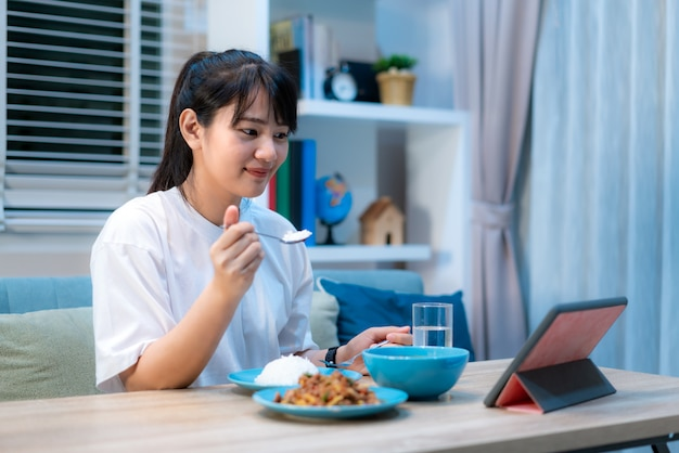 Premium Photo | Asian woman eating food in front of the laptop while having  an online call