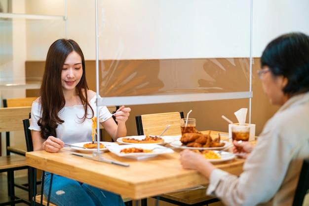 Азиатская женщина ест еду, сидя отдельно и соблюдая дистанцию с пластиковой перегородкой стола в ресторане Premium Фотографии