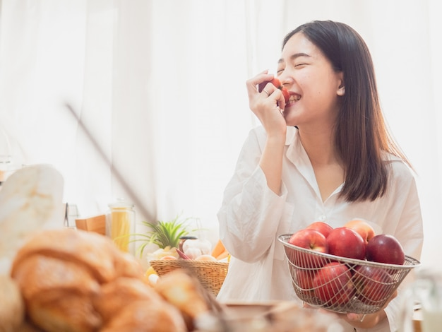 Asian woman eating fruit in the kitchen