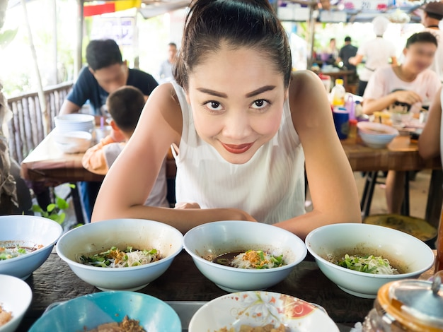 Premium Photo | Asian woman eating noodle in thai local restaurant in  thailand.