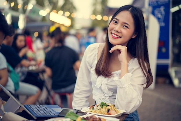 Азиатская женщина ест уличную еду, и она работает в своей компании Бесплатные Фотографии