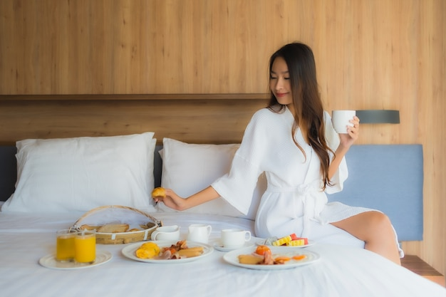 Asian woman enjoying with breakfast on bed Free Photo