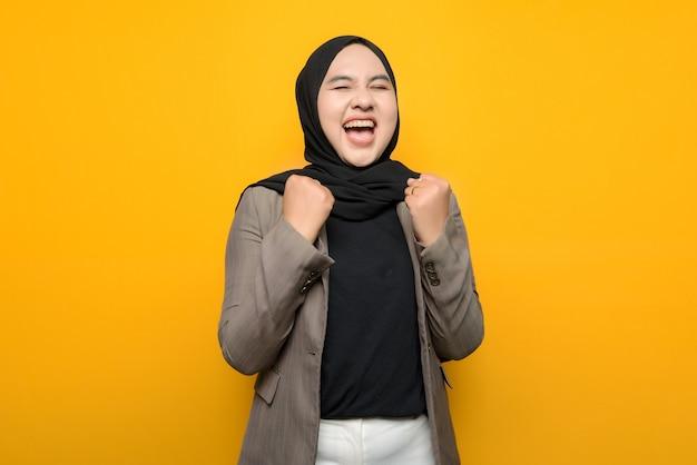 黄色の背景に興奮しているアジアの女性 Premium写真