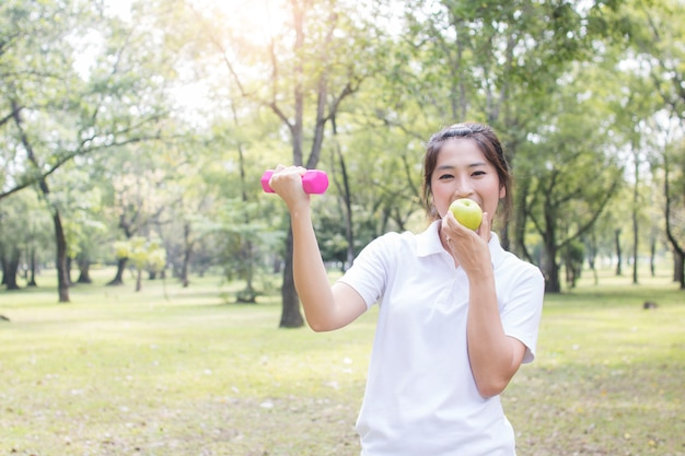 Asian woman exercise and workout lifting weight or pink dumbbell in park Premium Photo