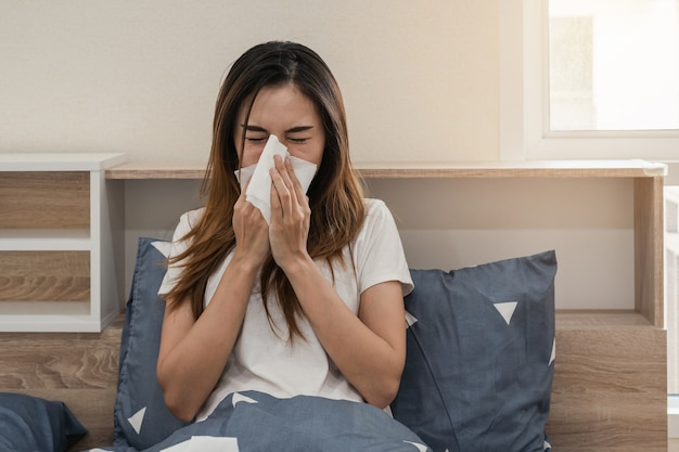 Asian woman feeling unwell and sneezing on the bed Premium Photo