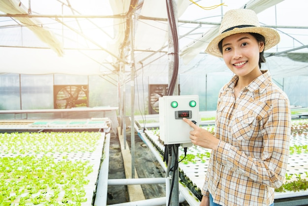 Asian woman finger press on temperature control machine in greenhouse hydroponic farm Premium Photo