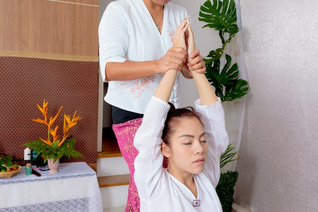 Asian woman getting traditional thai stretching massage by therapist Premium Photo