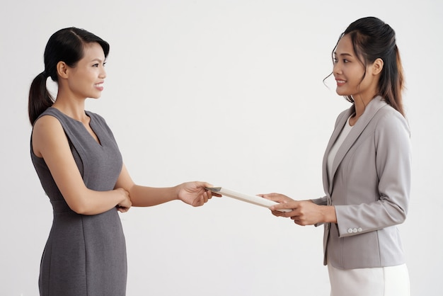 Asian woman giving document folder to her female boss in business suit at work Free Photo