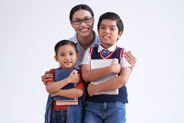Asian woman in glasses hugging two young schoolchildren Free Photo