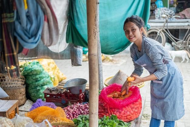 Овощная женщина азиатского происхождения достает морковь из мешков, чтобы выставить овощной прилавок на традиционном рынке Premium Фотографии