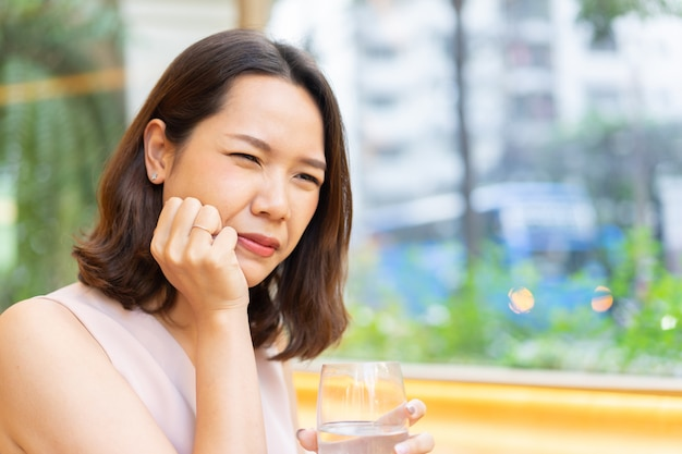 Asian woman  hand to massage cheek cause from toothache after drinking cold water for dental care Premium Photo