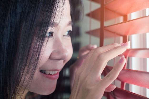Asian woman hands apart on the window blinds Premium Photo