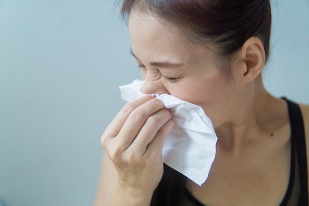 Asian woman has allergic rhinitis, sneezes into napkin, has headache. Premium Photo