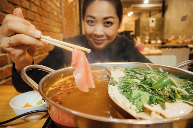 Asian woman have shabu style dinner for winter season. Premium Photo