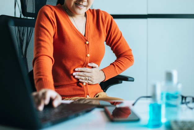 Asian woman having painful stomach ache during working from home Premium Photo