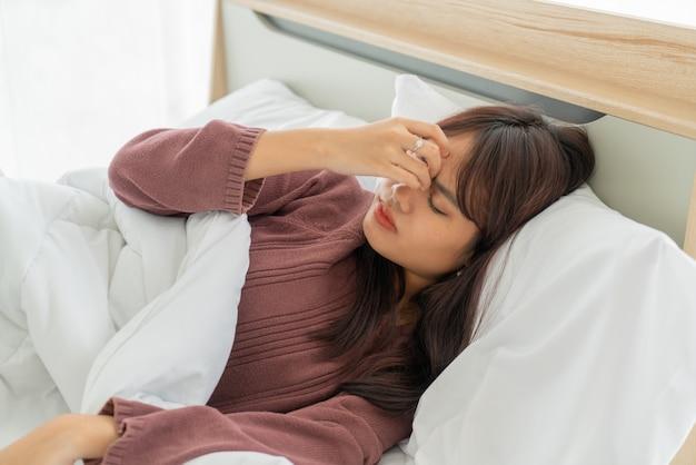 アジアの女性の頭痛とベッドで寝ています。 Premium写真